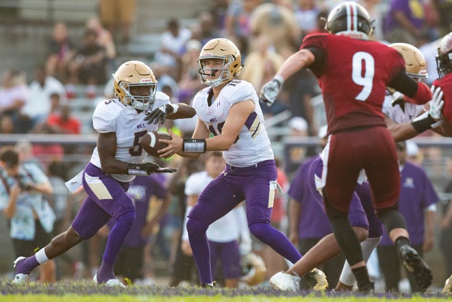 Male running back Quantrell Wright takes off with a handoff from quarterback Elijah Parish as No. 2 Male took on No. 4 Ballard on the Friday night gridiron at Louisville Male. August 30, 2019