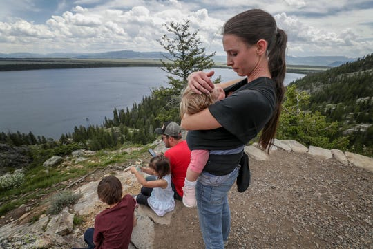 Rachael Denhollander holds her daughter at Inspiration Point in Jackson Hole, Wyoming.  Her husband, Jacob, is reading the Hobbit to their children.  She visited the area when she was a teen and brought her family along this time as she spoke to two groups during her trip to Wyoming. June 2019