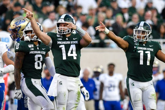 Brian Lewerke, left, and Connor Heyward, right, signal for a first down after a Lewerke run during the second quarter Friday.