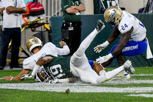 Michigan State's Josh Butler, center, dives after a loose ball in the Tulsa's end zone during the second quarter on Friday, August 30, 2019, at Spartan Stadium in East Lansing. At left, is Tulsa quarterback Zach Smith, left, and Corey Taylor II scramble for the ball as well. The Spartans scored a safety on the play.