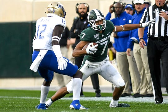 Michigan State's Cody White, right, catches a pass as Tulsa's Allie Green IV closes in during the first quarter on Friday, August 30, 2019, at Spartan Stadium in East Lansing.