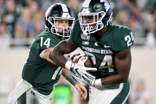 Michigan State's Brian Lewerke, left, hands the ball off to Elijah Collins during the fourth quarter on Friday, August 30, 2019, at Spartan Stadium in East Lansing.