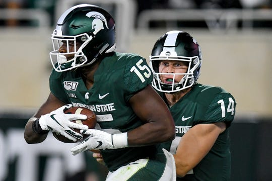 Michigan State's La'Darius Jefferson, left, runs with the ball after taking a handoff from Brian Lewerke, right, during the third quarter on Friday, August 30, 2019, at Spartan Stadium in East Lansing.