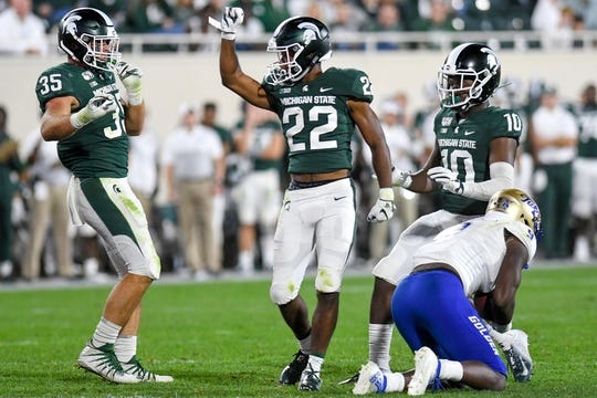 Michigan State's Josiah Scott, center, celebrates with teammates Joe Bachie, left, and Michael Dowell after a stop during the fourth quarter on Friday, August 30, 2019, at Spartan Stadium in East Lansing.
