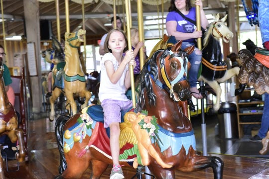 A girl rides a hand-carved horse Saturday at the Richland Carrousel Park.