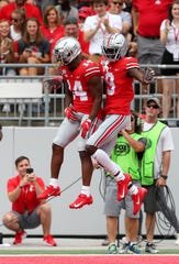 Ohio State wide receiver Binjimen Victor celebrates his first quarter touchdown catch with H-back K.J. Hill.