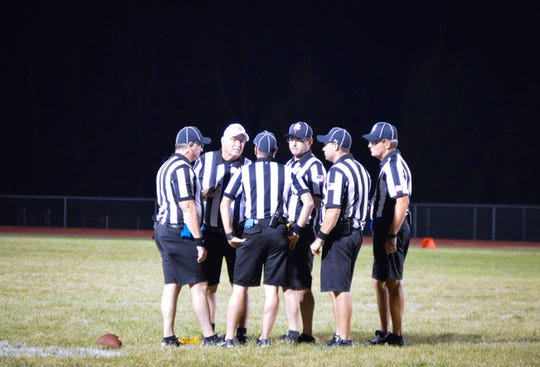 Football officials meet on the field during Week 1's Ridgemont at Ridgedale football game. The OHSAA said nearly 80 percent of officials drop out after two seasons due to unruly parents and fans and that is causing a shortage in qualified referees for all sports.