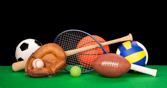 A collection of sports equipment such as a football, basketball, baseball, tennis racquet, volleyball, soccer ball and catcher's glove with a black background.