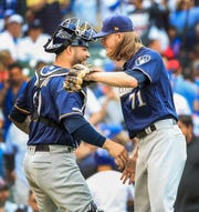 Josh Hader and catcher Manny Pina celebrate after the final out Saturday night against the Cubs.