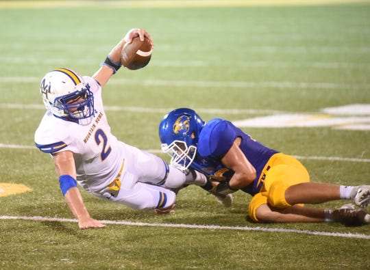 Mountain Home's Bryce McKay is brought down by a Sheridan defender on Friday night.