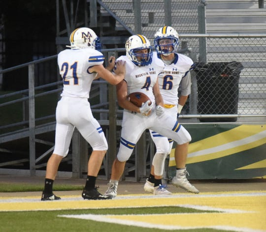Mountain Home's Tatem Beshears (4) celebrates a touchdown with teammates Adam Sorrell (21) and Logen Walker (6) on Friday night.