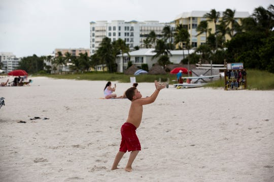 Local residents and visitors relax at Naples Beach on Aug. 31. The slow-moving Hurricane Dorian had an affect on hotels, restaurants and other businesses in Southwest Florida even though it remained off the east coast of Florida.