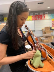 Teacher Shang Lee preparing string instruments for the upcoming school year.