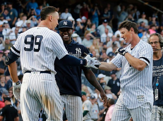 New York Yankees third baseman DJ LeMahieu (right) is congratulated by right fielder Aaron Judge (99) after hitting a game winning home run against the Oakland Athletics during the eleventh inning at Yankee Stadium.