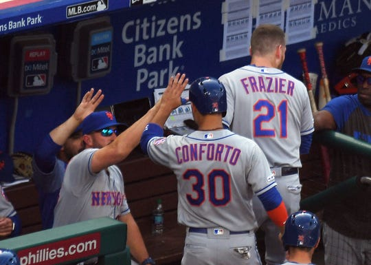 New York Mets right fielder Michael Conforto (30) is congratulated by manager Mickey Callaway (left) after he and third baseman Todd Frazier (21) scored runs in the fifth inning against the Philadelphia Phillies at Citizens Bank Park.