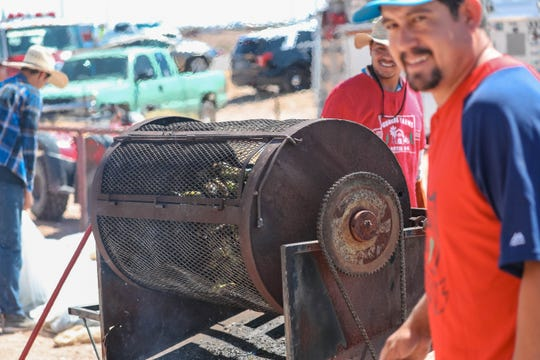 Alonso Grajeda, foreground, roasts chile at the Hatch Chile Festival in Hatch on Saturday, Aug. 31, 2019.