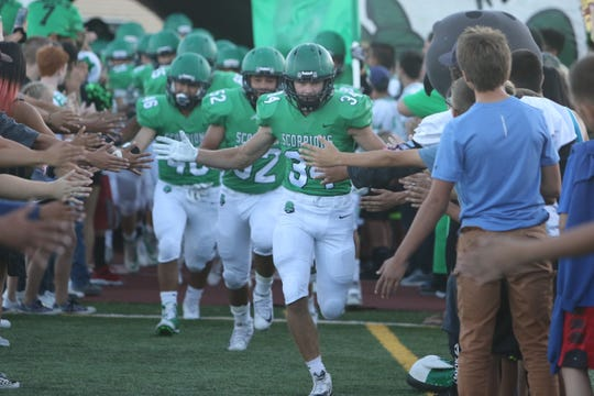 Cirrail Allison (34) leads the Farmington Scorpions out of the tunnel prior to Friday's football game at Hutchison Stadium in Farmington.