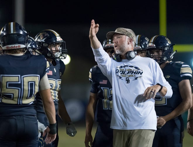 Dolphins head coach Bobby Clayton goes over a play in a timeout during the Catholic vs Gulf Breeze football game at Gulf Breeze High School on Friday, August 30, 2019.