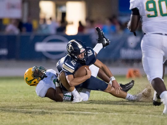 Sam Hooker (34) sack quarterback Ryland McClurdy (12) during the Catholic vs Gulf Breeze football game at Gulf Breeze High School on Friday, August 30, 2019.