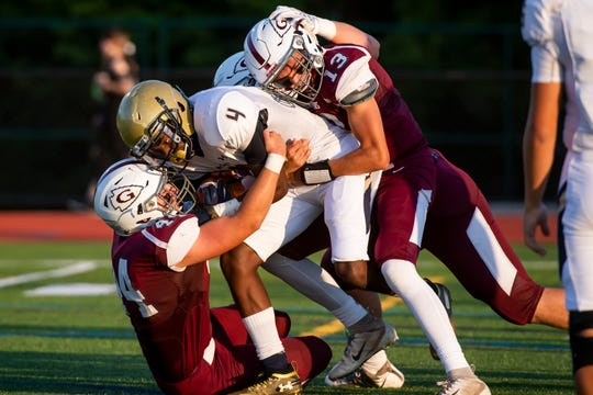 Gettysburg's Zach Ketterman (13), Gunner Pennington (44) and Frankie Richardson tackle Bishop McDevitt running back Dedrick Tinker (4) during a game at Warrior Stadium in Gettysburg on Friday, August 30, 2019. The Warriors fell, 28-9.