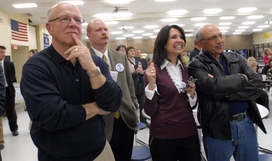 Rasha Demashkieh, middle, and her husband Walid, both of Fort Gratiot, watch a screen projecting election returns, Tuesday, May 3, 2011, along with then-Port Huron Schools Superintendent H. Ronald Wollen, left, Herb Wendt, then-school board vice president, inside the Port Huron Northern High School cafeteria. Demashkieh previously served on the school board for 13 years.