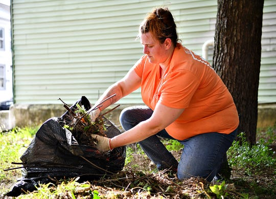 Brandi Cooper, of Manchester Township, throws branches into a pile as clean-up begins on East Charles Way as Black Star Action Network International launches the first York City Be Clean Campaign in York City, Saturday, Aug. 31, 2019. Cooper was one of a group of volunteers from the PoGo Community Outreach group. Dawn J. Sagert photo