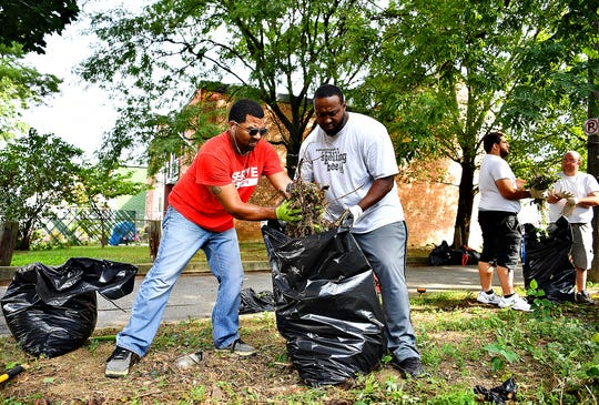 From left, Mark Macklin, of Springettsbury Township, Robert Jamison Jr., of Manchester Township, Seth Baker, of North York Borough, and Anthony Beck, of Dover Township, work together with more than a dozen volunteers to clean up properties at South Duke Street and East Charles Way as Black Star Action Network International launches the first York City Be Clean Campaign by cleaning up properties in the vicinity of East Charles Way and South Duke Street in York City, Saturday, Aug. 31, 2019. BSANI was founded in October 2017 in response to the devastating floods and mudslide in Freetown, Sierra Leone, West Africa, by Dennis' brother, Foday Ajamu Mansaray. Dawn J. Sagert photo