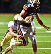 Delone Catholic's Michael O'Brien, back, works to pull down York Suburban's Isiaha Pineda during football action at York Suburban Senior High School in Spring Garden Township, Friday, Aug. 30, 2019. York Suburban would win the game 42-14. Dawn J. Sagert photo
