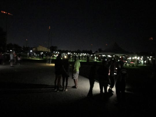 Spectators light the course with their phones after the lights went out during the high school girls race Friday night.