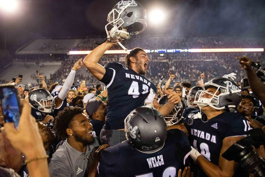 Nevada kicker Brandon Talton is mobbed by his teammates as he celebrates his game-winning field goal against Purdue on Friday night.