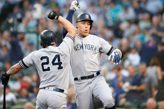 New York Yankees right fielder Aaron Judge (99) celebrates with a teammate after hitting a two-run home run against the Seattle Mariners during the first inning at T-Mobile Park on Aug. 27, 2019.
