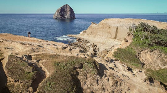 Visitors stand out on a rock to take in views of Cape Kiwanda State Natural Area. Where they are standing is not illegal, but it is beyond a barrier fence that rangers would prefer visitors to the park not cross.