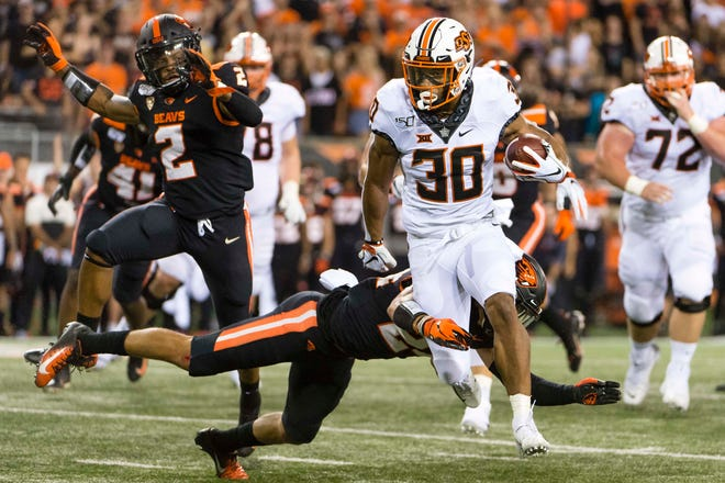 Aug 30, 2019; Corvallis, OR, USA; Oklahoma State Cowboys running back Chuba Hubbard (30) breaks away from Oregon State Beavers defensive back David Morris (24) for a first down during the first half at Reser Stadium. Mandatory Credit: Troy Wayrynen-USA TODAY Sports