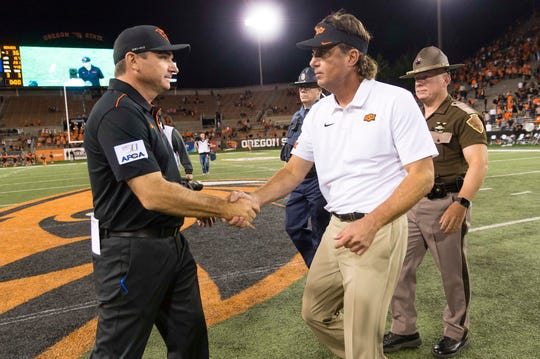 Aug 30, 2019; Corvallis, OR, USA; Oregon State Beavers head coach Jonathan Smith and Oklahoma State Cowboys head coach Mike Gundy shake hands after a game at Reser Stadium. Oklahoma State beat Oregon State 52-36. Mandatory Credit: Troy Wayrynen-USA TODAY Sports