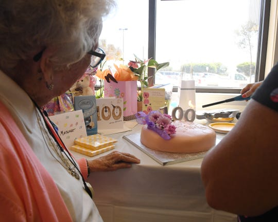 Someone lights the candles on Margaret Schlyter's 100th birthday cake. Aug. 31, 2019.