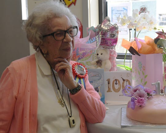 Margaret Schlyter poses next to her 100th birthday cake. Aug. 31, 2019.