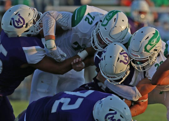 A player for Mason is wrapped up by the Wall defense during the season opener Thursday, August 29, 2019.