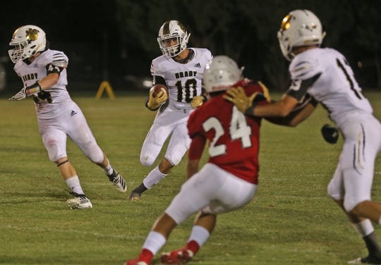 Benjamin Galindo, center, rushes the ball for Brady in the season opener against Ballinger on Friday, August 30, 2019.