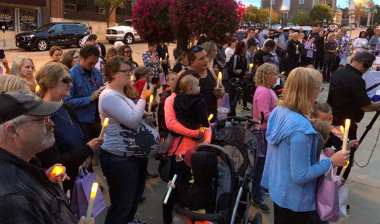 Cheryl Howe and Ashley Hayden hold candles in front of the Sioux Falls City Hall building in downtown Sioux Falls on Friday. The two, and other members of their family, honored the memory of Danielle Howe, who died from fentanyl overdose in 2014.