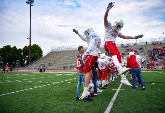 Two Brandon Valley Lynx jump at each other as they are introduced before the start of their game against Roosevelt Rough Riders on Friday, August 30, at Howard Wood Field in Sioux Falls.