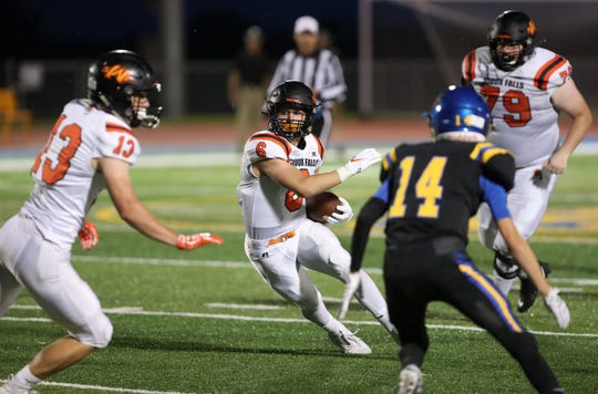 Sioux Falls Washington's Luke Behrens (6) finds an opening as Aberdeen Central's Avery Bad Moccasin (14) closes in on defense during Friday night's game at the Hub City Bowl in Aberdeen at Swisher Field. In on the play for the Warriors are Carson Strom (13) and Jared DeBoer (79). American News photo by John Davis taken 8/30/2019