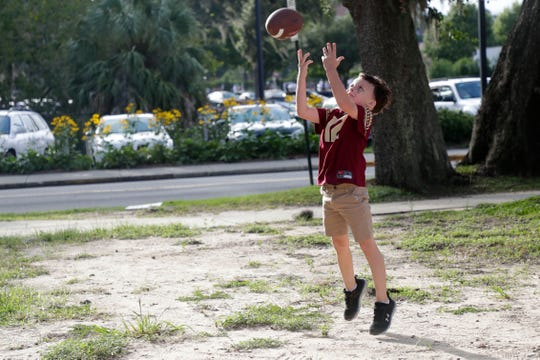 Lucas Priester catches a football as he plays by himself before experiencing his first Seminole football game.