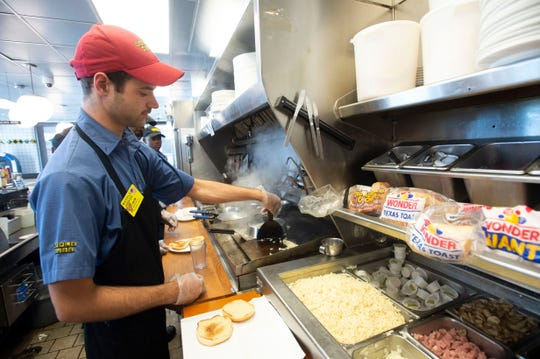 Jacob Duncan, Waffle House #443 master grill operator, cooks up hash browns ahead of Hurricane Dorian on Saturday, Aug. 31, 2019, in Fort Pierce, Florida.