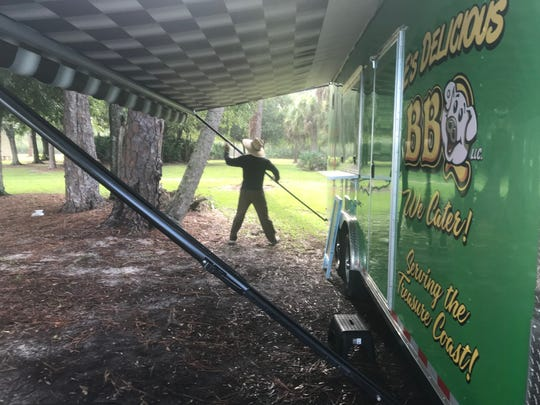 """Eli Valdes, of Vero Beach, sets up his mobile food truck E's Delicious BBQ,  Saturday, Aug. 31, 2019, on Emerson Avenue and Indrio Road as he has done every weekend for the past year despite Hurricane Dorian churning in the Atlantic Ocean and threatening to make landfall on the Treasure Coast. """"It's a nice day. Why sit at home worrying about what could happen a few days from now? All you can do is prepare and trust God with the rest."""""""