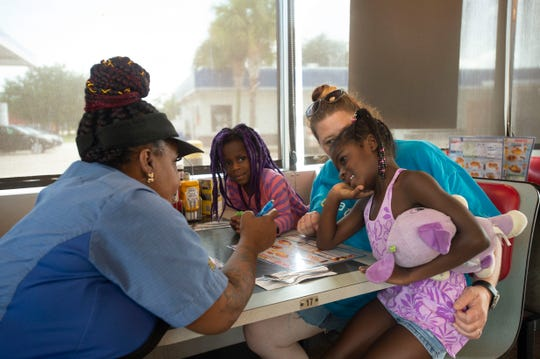 Lisa English, left, Waffle House #443 salesperson, interacts with the Bahm family, from left, Ella, 4, Jenny, and Tiana, 5, of Lake Worth, Florida, who stopped by for a meal as they evacuated toward Tallahassee ahead of Hurricane Dorian on Saturday, Aug. 31, 2019, in Fort Pierce.