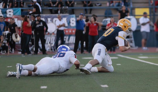 Dylan Kemp (white) gets one of his five first-quarter sacks against Eastwood quarterback Christian Casteneda in the first quarter Friday night