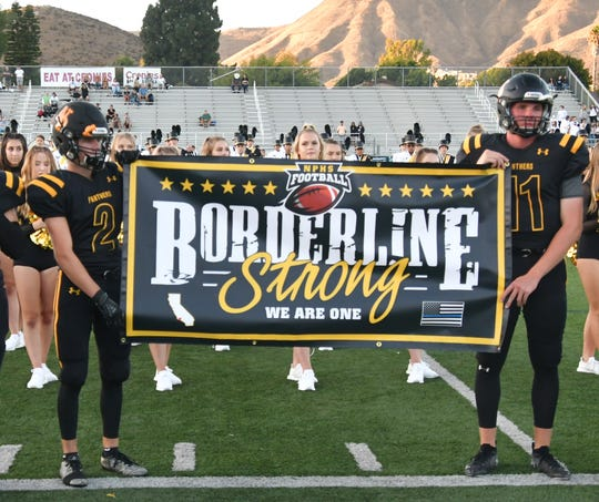 Newbury Park seniors Soren Brown, left, and Ben Gulbranson present a banner in memory of the 12 victims of the Borderline shooting that was hanged under the Hurley Field scoreboard before the Conejo rivalry's 51st meeting on Friday night. Newbury Park beat Thousand Oaks, 44-21.