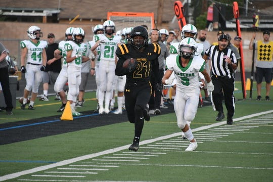Newbury Park junior Christian Middleton races down the sideline for his second of three touchdowns on Friday night against Thousand Oaks. Newbury Park won the Conejo rivalry's 51st meeting, 44-21.