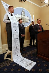 In this Jan. 8. file photo, Democratic staff member William Pond, left, wears an enlarged mock-up of a receipt as Assemblyman Phil Ting, D-San Francisco, right, discusses his bill to require businesses to offer electronic receipts, in Sacramento.