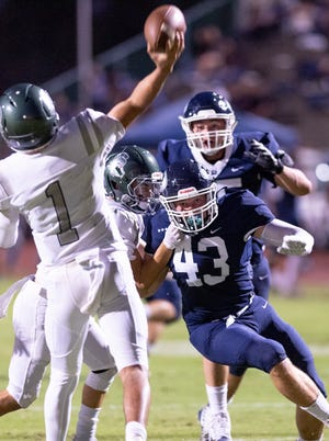 Redwood's Hudson Walker eyes Dinuba quarterback Josh Magana at Mineral King Bowl in a non-league football game on Friday, August 30, 2019.